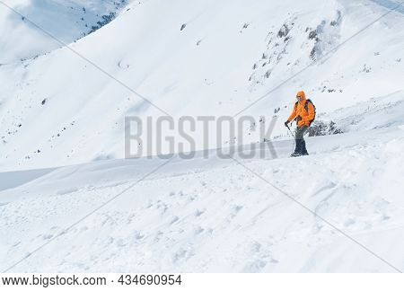 High Mountaineer Dressed Bright Orange Softshell Jacket Using A Trekking Poles Ascending The Snowy M
