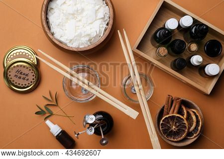 Flat Lay Composition With Ingredients For Homemade Candles On Brown Background