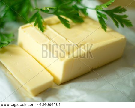 Sliced butter Pieces And Decorated With A Green Leaf Of Fresh Parsley