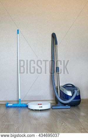 White Robotic Vacuum Cleaner Next To A Conventional Vacuum Cleaner And A Mop On Laminate Wood Floor