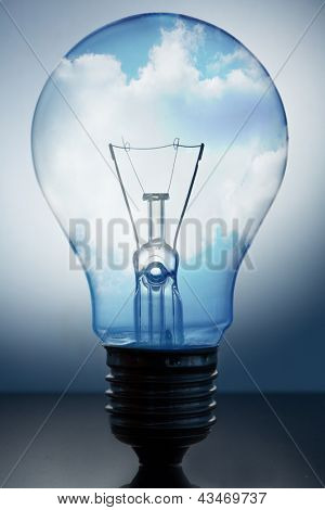 Close up of big light bulb standing with bright blue sky with clouds in it