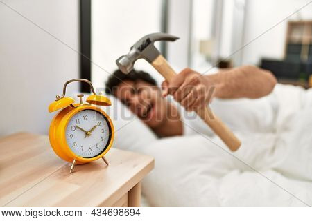 Young hispanic man turning off alarm clock using hammer lying on the bed at bedroom.