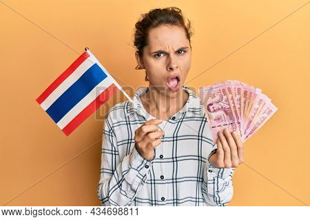 Young brunette woman holding thailand flag and baht banknotes in shock face, looking skeptical and sarcastic, surprised with open mouth