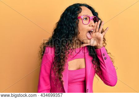 Young latin woman wearing business style and glasses shouting and screaming loud to side with hand on mouth. communication concept.