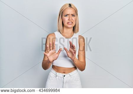 Beautiful blonde woman wearing casual style with sleeveless shirt disgusted expression, displeased and fearful doing disgust face because aversion reaction. with hands raised