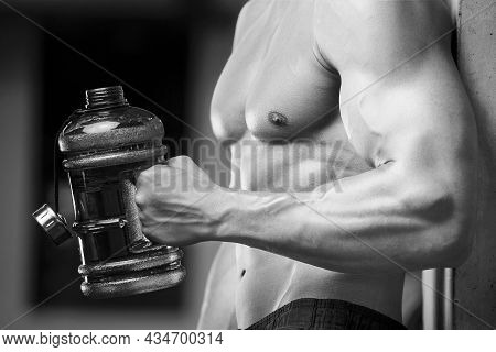 Young Athletic Man Pumping Up Muscles In The Gym At Workout. Sport And Health Care Concept Backgroun