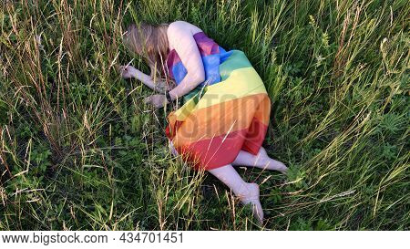 Lesbian Woman Lying On Lgbt Flag On Grass In White Dress. Support Of Non-traditional Orientation In