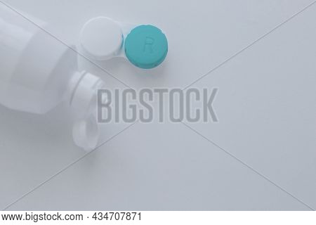 The Lens Container And The Lens Storage Liquid Lie On The Side On A White Background With Space For