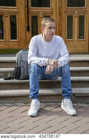 A Young Guy Of 20-25 Years Old In Summer Clothes With A Backpack Is Sitting On The Steps At The Entr