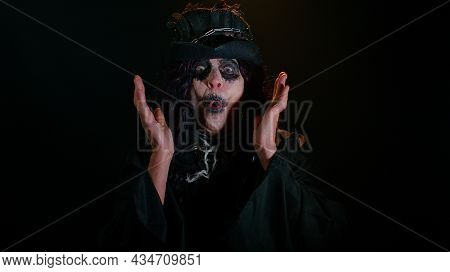 Wow. Frightening Senior Woman With Halloween Witch Makeup Raising Hands In Surprise Looking At Camer