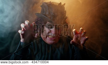 Sinister Elderly Man With Horrible Scary Halloween Witcher Makeup In Costume Making Faces, Looking O