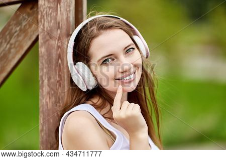 Portrait Of Smiling Woman 29 Years Old In Wireless Headphones In Park.