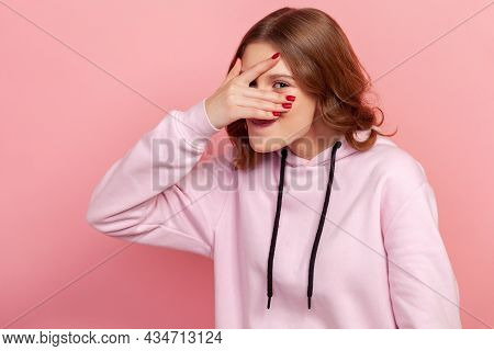 Portrait Of Curious Teenager Female In Hoodie Spying, Hiding And Peeping Through Fingers, Looking Fo