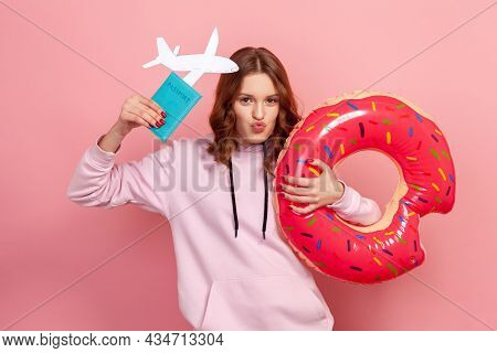 Portrait Of Pleased Curly Haired Teenage Girl In Hoodie With Pout Lips Showing Donut Rubber Ring, Pa
