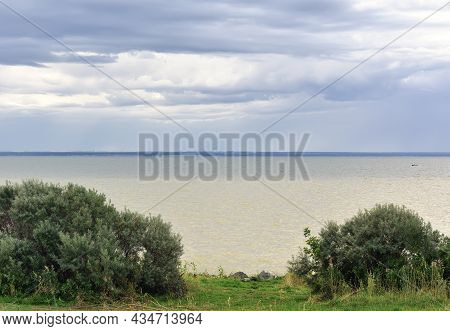 The Green Coast Of The Ob Sea With Bushes, The Water Surface Under A Blue Sky With Cumulus Clouds. B