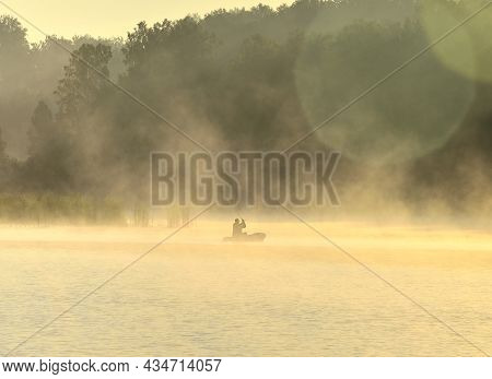 Morning On The Shore Of A Forest Lake, A Fisherman On An Inflatable Boat Floating On The Water In Cl
