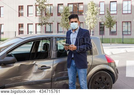 Young Adult Brunette Man In Surgical Medical Mask, Jacket And Jeans Posing On City Street With Digit