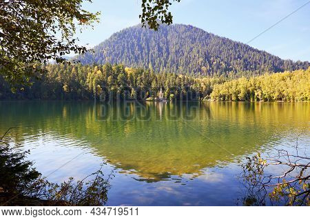 A Beautiful Autumn Landscape.reflection Of The Mountain And Trees In The Lake. Orthodox Chapel On Th