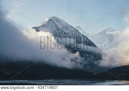 Beautiful View Of Snow-capped Mountains Above Thick Clouds In Sunshine. Scenic Mountain Landscape Wi