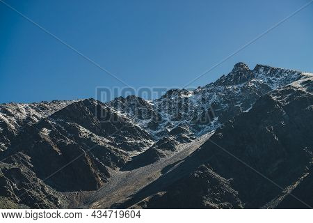 Minimal Mountain Landscape With Black Peaked Top With White Snow Under Blue Sky. Snow-covered Pointy