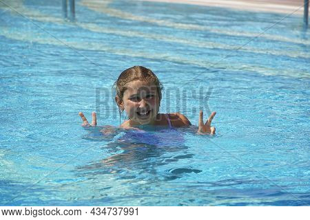 Little Girl At Swimming Pool. Smiling Girl Having Fun In Swimming Pool On Summer Vacation. Swimming
