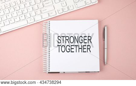 Pink Office Desk With Keyboard, Notebook With Text Stronger Together