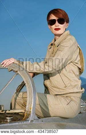 Professional commercial pilot woman wearing uniform and sunglasses sits in her aircraft cockpit ready for take off. Aviation.