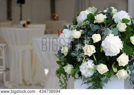 White Roses In Flower Arrangement For A Reception With Defocussed Tables With White Napkins