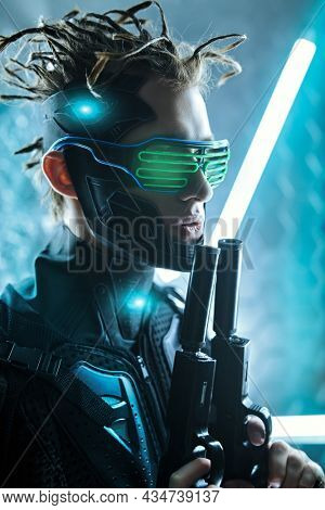 Warrior of the future. A cool cyberpunk warrior in sci-fi armor and cyber glasses standing in neon lights on alert with guns in his hands. Game, virtual reality.