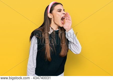 Young beautiful woman wearing casual white shirt shouting and screaming loud to side with hand on mouth. communication concept.