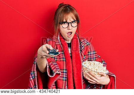Redhead young woman eating popcorn using tv control in shock face, looking skeptical and sarcastic, surprised with open mouth