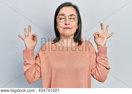 Middle age hispanic woman wearing casual clothes and glasses relax and smiling with eyes closed doing meditation gesture with fingers. yoga concept.