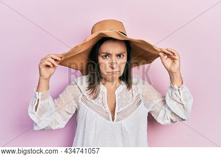 Middle age hispanic woman wearing summer hat skeptic and nervous, frowning upset because of problem. negative person.