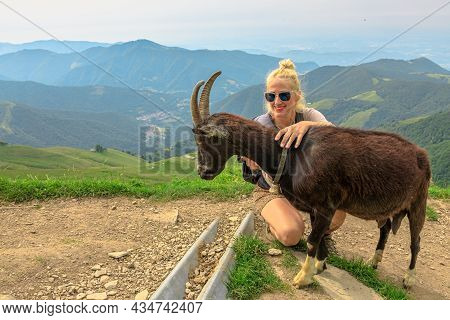 Tourist Backpacker Petting A Goat In Switzerland By The Panorama From Monte Generoso Peak. Top Of Me
