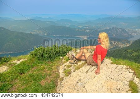 Tourist Woman In Trekking Dress On Top Of Monte Generoso Aerial View Or Calvagione Swiss Mount. Luga