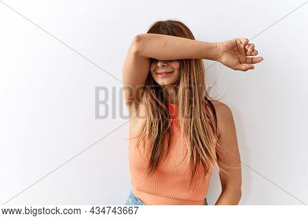 Hispanic woman with bang hairstyle standing over isolated background covering eyes with arm smiling cheerful and funny. blind concept.