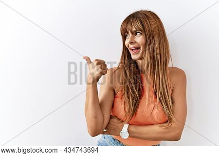 Hispanic woman with bang hairstyle standing over isolated background smiling with happy face looking and pointing to the side with thumb up.