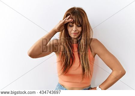 Hispanic woman with bang hairstyle standing over isolated background worried and stressed about a problem with hand on forehead, nervous and anxious for crisis
