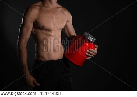Athletic Man With Big Red Jar On Black Background, Closeup. Doping Concept