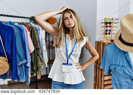 Young blonde woman working as manager at retail boutique confuse and wonder about question. uncertain with doubt, thinking with hand on head. pensive concept.