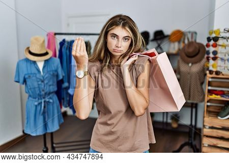 Young blonde woman holding shopping bags at retail shop doing italian gesture with hand and fingers confident expression