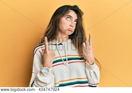 Young caucasian woman wearing casual clothes pointing up looking sad and upset, indicating direction with fingers, unhappy and depressed.