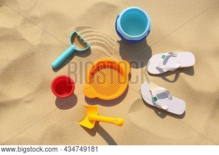 Set Of Plastic Beach Toys And Flip Flops On Sand, Flat Lay. Outdoor Play