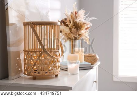 Burning Scented Candles And Bouquet On White Chest Of Drawers In Room