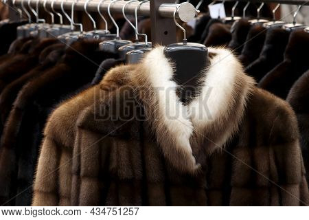 Fur Coats In A Row On A Hanger In The Store. Female Fashion, Natural Fur Clothes In Sale