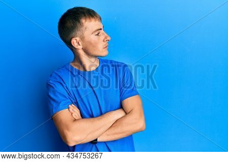 Young caucasian man wearing casual blue t shirt looking to the side with arms crossed convinced and confident