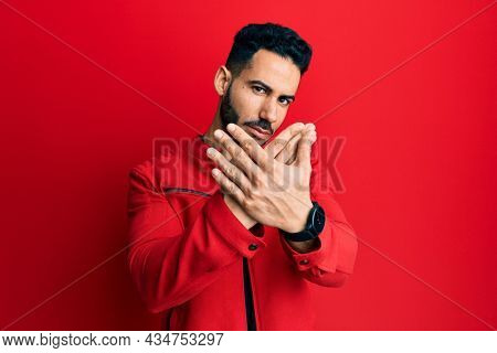 Young hispanic man wearing red leather jacket rejection expression crossing arms doing negative sign, angry face