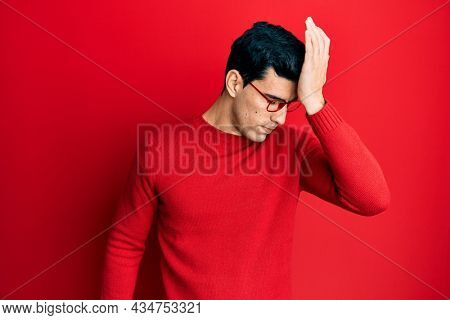 Handsome hispanic man wearing casual clothes and glasses surprised with hand on head for mistake, remember error. forgot, bad memory concept.
