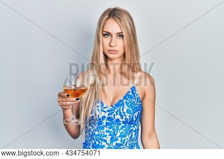 Young beautiful caucasian woman drinking a glass of white wine skeptic and nervous, frowning upset because of problem. negative person.