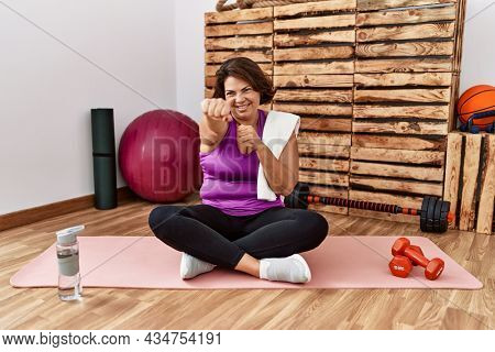 Middle age hispanic woman sitting on training mat at the gym punching fist to fight, aggressive and angry attack, threat and violence